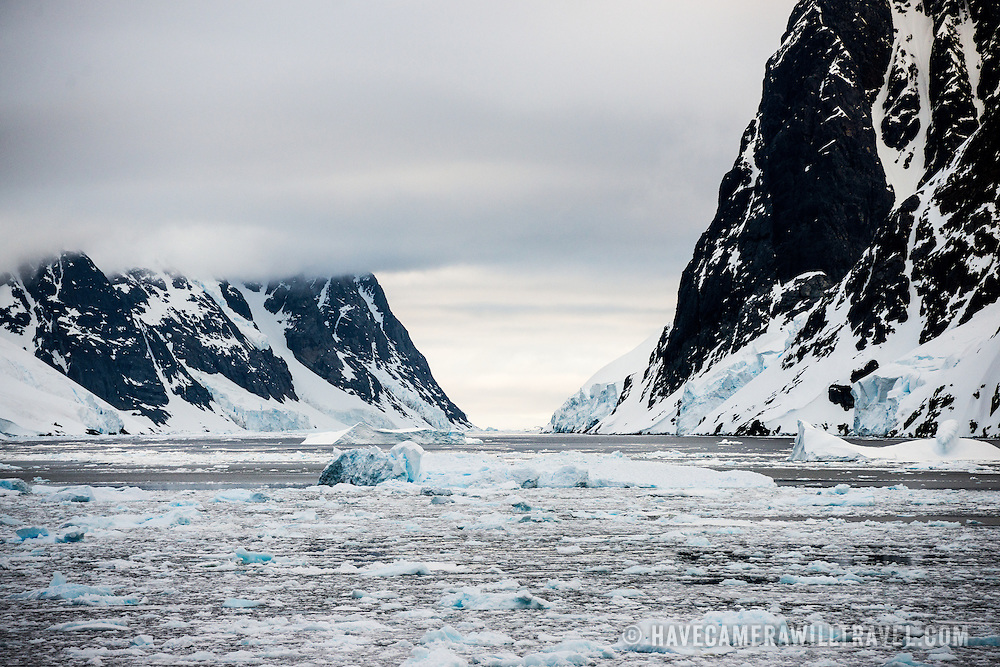 "Sheets of sea ice and brash ice fkoat on the water of the Lemaire Channel, with steep mountain cliffs rising out of the water on either side. The Lemaire Channel is sometimes referred to as ""Kodak Gap"" in a nod to its famously scenic views."