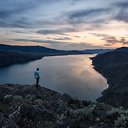 A hiker watches the sun set over Kamloops Lake from the Battle Bluff.