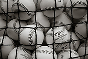 Detail photo of baseballs piled in a batting practice bin with Major League Baseball and Rawlings logo prominent. Seattle Mariners at Texas Rangers. Photographed at Rangers Ballpark In Arlington in Arlington, Texas on Sunday, April 11, 2010. Photograph © 2010 Darren Carroll.