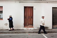 """PERDASDEFOGU, SARDINIA, ITALY - 29 JUNE 2013: An elderly woman and man walk in the main street of Perdasdefogu, Italy, on June 29th 2013. Today Perdasdefogu has two pensioners for every worker, an average age of 47, and an unemployment rate of around 25 percent. Between 2001 and 2011, the number of centenarians in Italy rose 138 percent, and that of nonagenarians rose 78 percent. Today, 20 percent of Italians are over the age of 65.<br /> <br /> Last year, the Melis family entered the Guinness Book of World Records for having the highest combined age of any nine living siblings on earth — today more than 825 years. The youngest sibling, Mafalda – the """"little one"""" – is 79 years old.<br /> <br /> The Melis siblings were all born in Perdasdefogu to Francesco Melis and Eleonora Mameli, who had a general store. Consolata, 106, is the oldest, then Claudia, 100; Maria, 98; Antonino, 94; Concetta, 92; Adolfo, 90; Vitalio, 87; Fida Vitalia, 81; and Mafalda, the baby at 79. Their descendants now account for about a third of the village."""