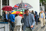 A spectator shelters from the rain under an umbrella ahead of the International Test Match 2019 match between England and Australia at Lord's Cricket Ground, St John's Wood, United Kingdom on 14 August 2019.