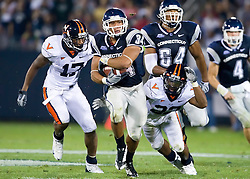 Connecticut running back Donald Brown (34) beats Virginia safety Brandon Woods (17) and Virginia safety Byron Glaspy (22) to break a 63 yard touchdown run against UVA.  The Connecticut Huskies defeated the Virginia Cavaliers 45-10 in NCAA football at Rentschler Field in East Hartford, CT on September 13, 2008.
