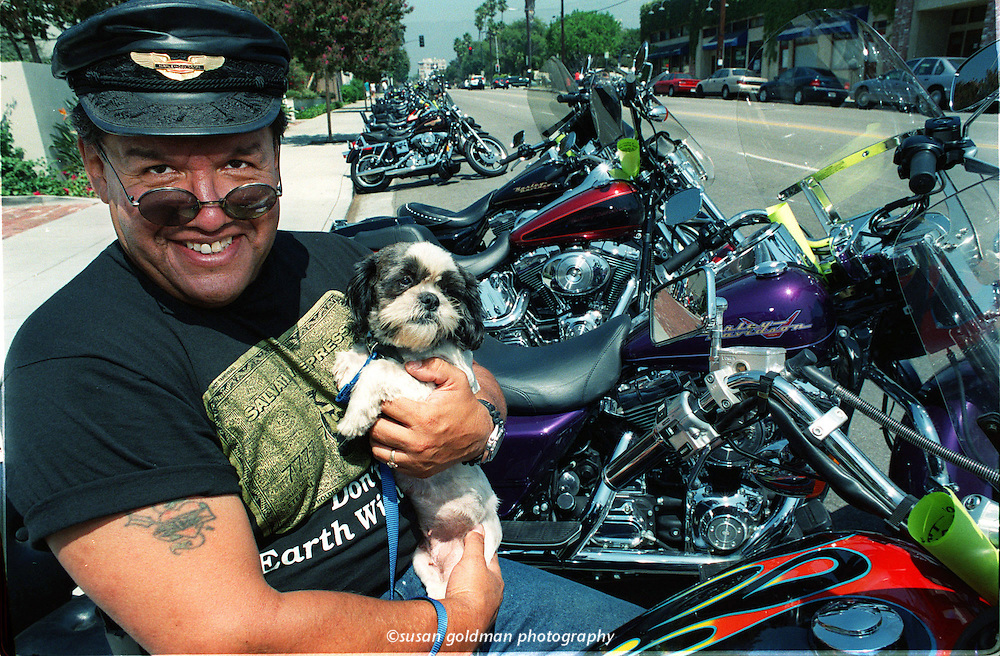 Michael Flores, a Rowland Heights, Calif., real estate agent, holds Lacy, a Shih Tzu, as he sits on his Harley Davidson motorcycle at the Hogs for Dogs event at the Pasadena, Calif., Humane Society fundraiser. Photo/Pasadena Humane Society, Susan Goldman.