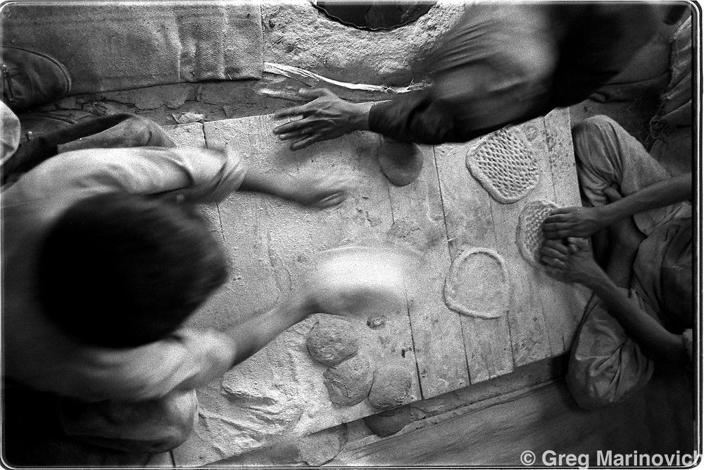 Afghans make their naan or flat bread in a bakery in Bazarak, Sept 1999. (Greg Marinovich)