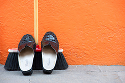 Shoes resting on broom outside brightly painted orange house in Burano near Venice Italy