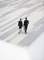 Businessman and businesswoman walking across outdoor plaza elevated view back view