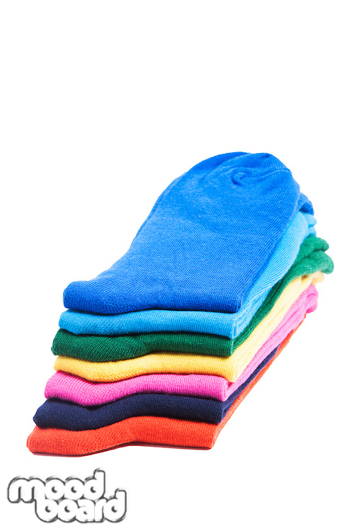Colorful pile of folded socks over white background