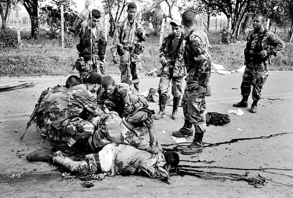 A dead Government soldier lies in the road while his collegues treat a companion who was wounded when a FARC planted bomb exploded in a bus they were searching. The bus was part of a roadblock built to facilitate the kidnap of Ingrid Betancourt on the 23rd February.<br />