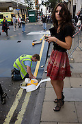 As a Dior employee oversees her company's PR event, an outdoor set is constructed for the Christian Dior fashion house in London's Bond Street during Vogue's Fashion's Night Out festival in the streets of the West End. A contracted workman wearing high-vis tabard vests put the finishing touches to a raised ramp that a Dior-sponsored taxi cab will be placed upon, complete with fake double-yellow lines. The fake road surface has been laid out after other workmen prepared a Dior street sign and staple parts of the ramp together.