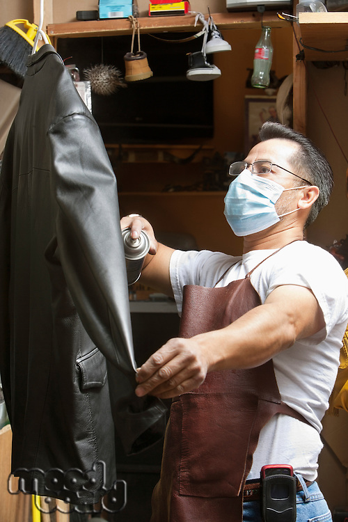 Mature cobbler wearing mask looking at leather jacket in workshop