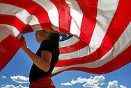 Xavier Mascareñas/New Mexico Daily Lobo; Albuquerque, N.M., 9-year-old Jenny Saenz holds an American flag at an immigration rally at Tiguex Park on May 1, 2006, to protest legislation in Washington, D.C., seeking to reform immigration.