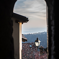 A view on the lakes seen from a dark passsage in Santa Maria Del Monte in Varese, Italy