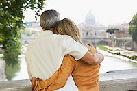 Couple on bridge in Rome Italy looking at view of cathedral back view