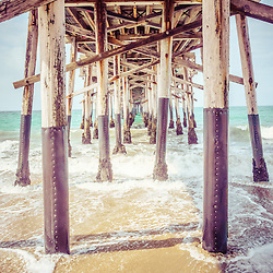 Under the pier in Southern California picture of the wooden posts that support Balboa Pier. Balboa Pier is on Balboa Peninsula in Newport Beach, Orange County, California. Photo has a vintage 1950s tone.