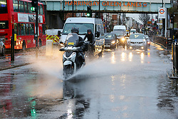 © Licensed to London News Pictures. 15/01/2020. London, UK. A motorbike drives through a flood on Green Lanes in north London following heavy overnight rainfall. Photo credit: Dinendra Haria/LNP