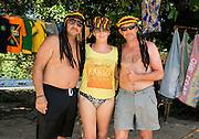 Tourist friends model dreadlock Jamaican hats on the beach, Negril, Jamaica