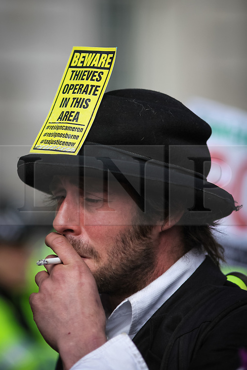 © Licensed to London News Pictures. 09/04/2016. London, UK. A protestor outside Downing Street as thousands gather on Whitehall to demand that British Prime Minister David Cameron resign after he admitted to profiting from the sale of shares worth more than £30,000 in Blairmore Holdings, an offshore investment fund set up by his late father Ian Cameron. The Panama Papers, leaked anonymously from the database of law firm Mossack Fonseca, have revealed the extent to which firms and wealthy individuals use loopholes and offshore funds to avoid paying tax. Photo credit: Rob Pinney/LNP