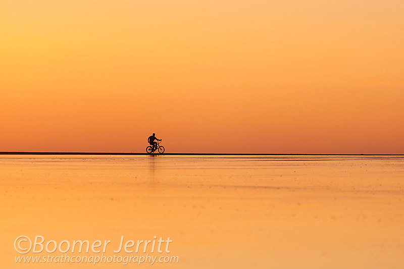 A lone person riding a beach cruiser along Chesterman Beach at low tide, heads home after sunset.  Chesterman Beach, Tofino, Vancouver Island, British Columbia, Canada