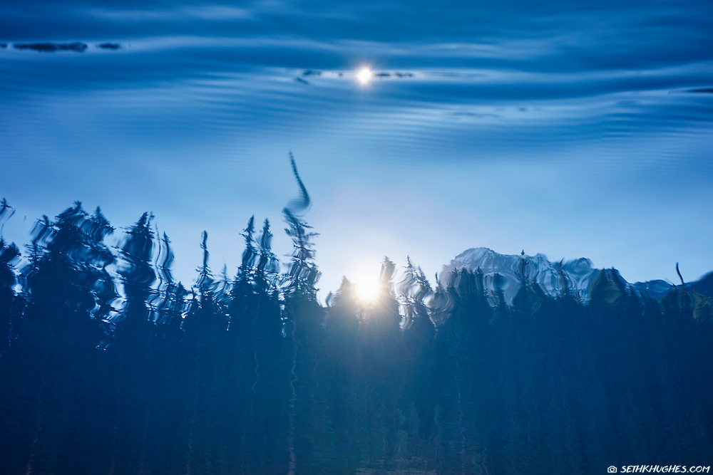 A blue, alipine lake reflection on Moraine Lake, Banff National Park, Alberta, Canada.