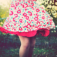 Close up of young woman outside wearing summer dress with red flowers