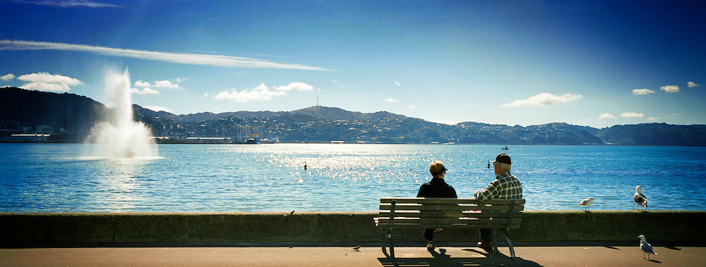 A couple sits on a bench at Oriental Parade, Wellington, New Zealand