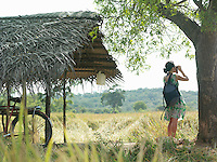 Young woman looking through binoculars bicycle under thatched roof