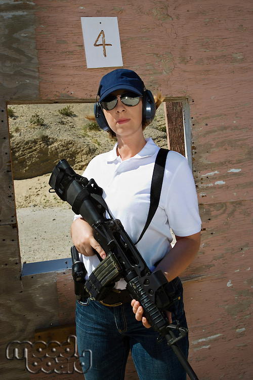Woman holding machine gun at firing range, portrait