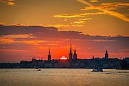 Gamla stan i Stockholm från vattnet i solnedgång med kyrkor och Stadshuset.