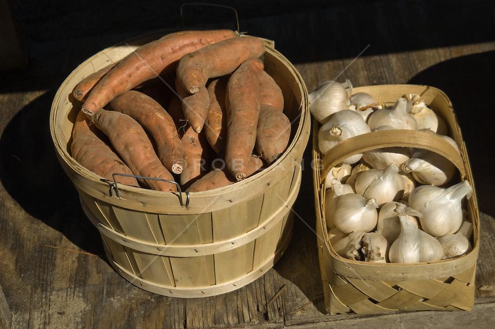 Bushel of sweet potatoes and a basket of elephant garlic