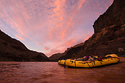 The early sky above the Colorado River is painted with warm morning light as the sun rises over the Grand Canyon. In the foreground are our rafts that we are preparing for our last day of an 18day, 225-mile trip down the river through the canyon.
