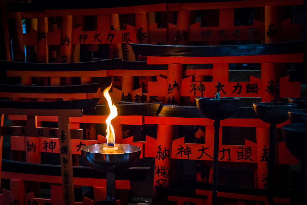 A candle burns near a set of small red tori, in one of the many small alcoves along the path in Fushimi Inari. This is one of the many forms of asking for the divine intervention of the Kami Inari.
