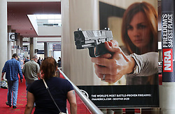 April 27, 2017 - Atlanta, Georgia, U.S. - Attendees pass by a large banner advertising a handgun during the NRA convention at the Georgia World Congress Center on Thursday. President Donald J. Trump will keynote the National Rifle Association Leadership Forum at the convention on Friday. (Credit Image: © Curtis Compton/TNS via ZUMA Wire)
