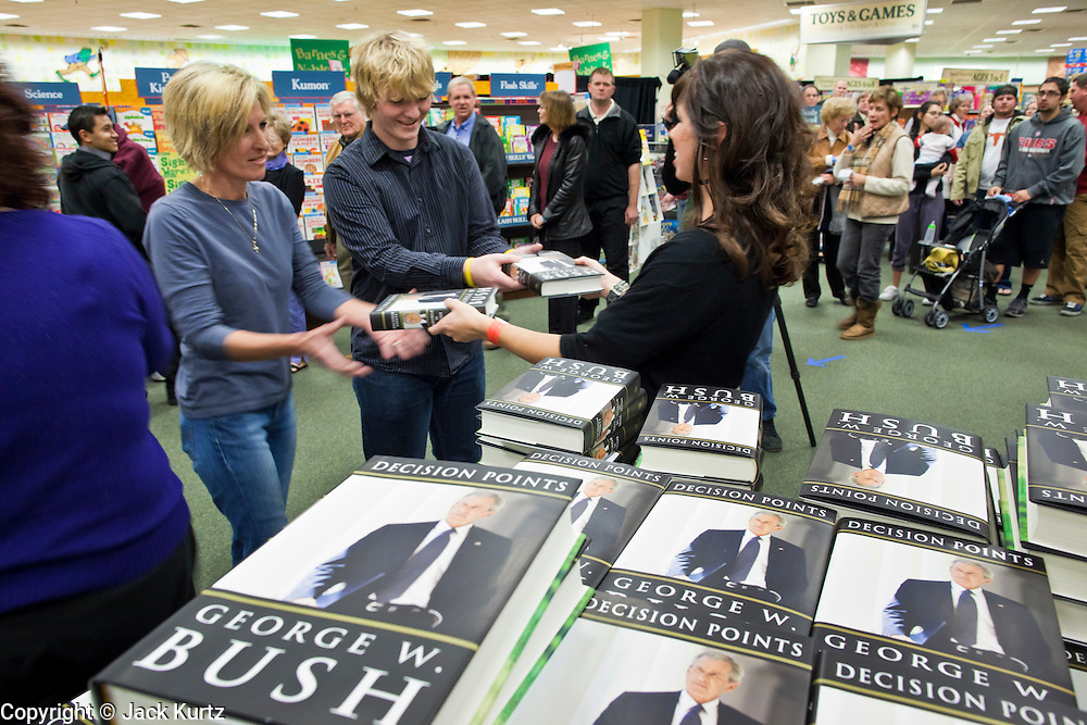 """09 DECEMBER 2010 - PHOENIX, AZ: KATIE RAY, a Barnes & Noble assistant manager hands out copies of George W, Bush's book at the Barnes & Noble Bookstore in Phoenix, AZ, Thursday, Dec. 9. More than 2,000 people lined up starting at 5AM to get copies of the former President's book, """"Decision Points."""" A handful of protesters demonstrated against President Bush near the bookstore, calling him a """"war criminal.""""   PHOTO BY JACK KURTZ"""