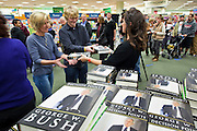 "09 DECEMBER 2010 - PHOENIX, AZ: KATIE RAY, a Barnes & Noble assistant manager hands out copies of George W, Bush's book at the Barnes & Noble Bookstore in Phoenix, AZ, Thursday, Dec. 9. More than 2,000 people lined up starting at 5AM to get copies of the former President's book, ""Decision Points."" A handful of protesters demonstrated against President Bush near the bookstore, calling him a ""war criminal.""   PHOTO BY JACK KURTZ"