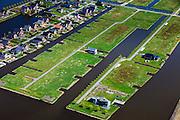 Nederland, Groningen, Oldambt, 01-05-2013; Blauwestad, nieuw aangelegd woongebied inclusief recreatiegebied. Het Oldambtmeer dient ook als waterberging. Wijk 'De Wei' met kavels voor zelfbouw, nog maar gedeeltelijk bebouwd.<br /> Het project Blauwe Stad was oorspronkelijk bedoeld om de economisch achtergebleven regio van Noordoost Groningen een impuls te geven. De economische en huizen crisis gooit echter roet in het eten.<br /> Blauwestad (Blue City) newly constructed residential area, including recreational lake. The Oldambt lake also serves as water storage. Area 'De Wei' (Meadow) with plots suited for 'DIY' buidling of houses. The Blue City project is meant to give a boost to the  economically backward region of northeast Groningen.<br /> luchtfoto (toeslag); aerial photo (additional fee required);<br /> foto Siebe Swart / photo Siebe Swart
