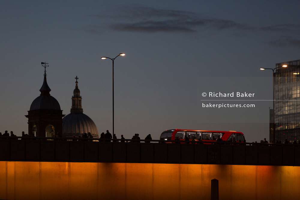 Evening rush-hour commuters and a London bus cross London Bridge (with the dome of St Paul's Cathedral) after the beginning of winter time, on 29th October 2018, in London, England.