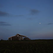 Moon rise over an isolated property on Cisco Beach, Nantucket, Nantucket Island, Massachusetts, USA. Photo Tim Clayton