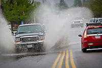 A motorist splashes through standing water at U.S. 95 and Canfield Avenue following a downpour Thursday.