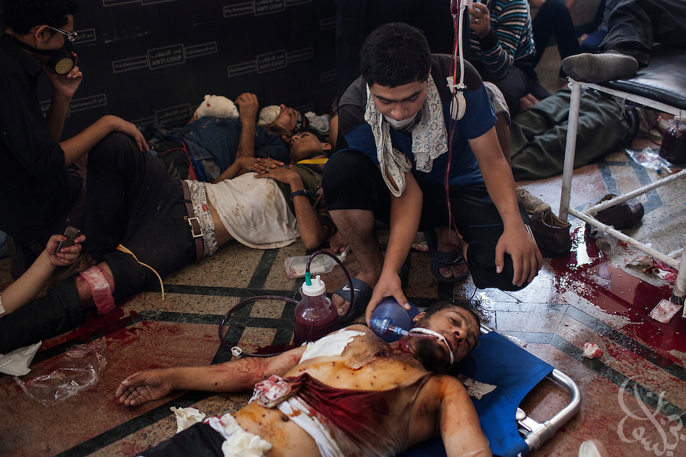 A critically injured man is a given assisted breathing inside a packed field hospital inside the Rabaah al-Adawiya protest camp in Nasr City during the August 14, 2013 Ministry of Interior/Police operation to clear the protest by force. The assault, which began at 7am with police moving in to seal the surrounding streets included tear gas and live fire, and there are reports of large numbers of killed and wounded protesters.