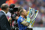 AFC Wimbledon defender Barry Fuller (2) kissing the trophy during the Sky Bet League 2 play off final match between AFC Wimbledon and Plymouth Argyle at Wembley Stadium, London, England on 30 May 2016.