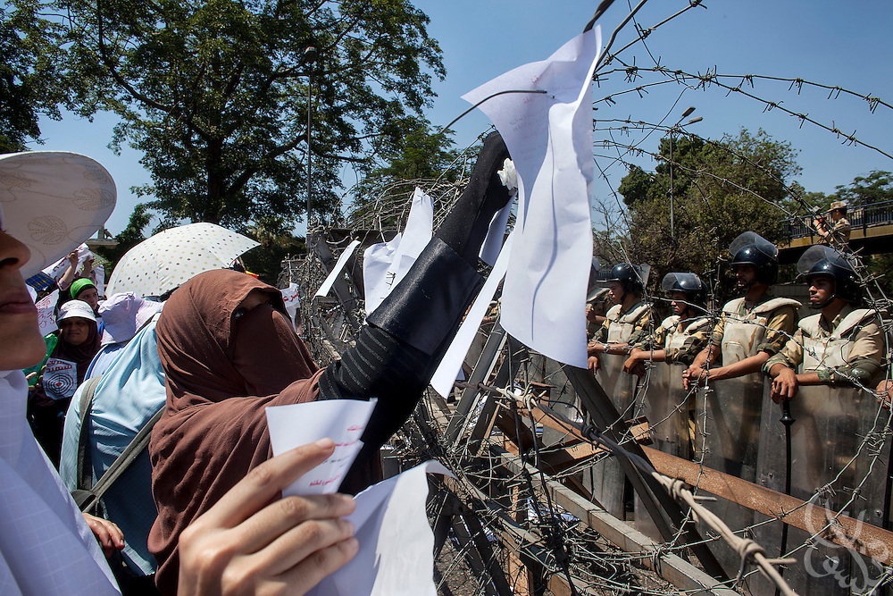 Female Muslim Brotherhood members and supporters of deposed Egyptian president Mohamed Morsi post pro-Morsi pamphlets on the barbed wire barricade manned by Egyptian soldiers on the road leading to the the Defense Ministry in the Abbasiya district of Cairo during a protest there  Friday July 30, 2013.  The Muslim Brotherhood has maintained a steady wave of protests and sit-ins for a month since Morsi was deposed by the Egyptian military and replaced by an interim government, and vow to continue until he is reinstated.