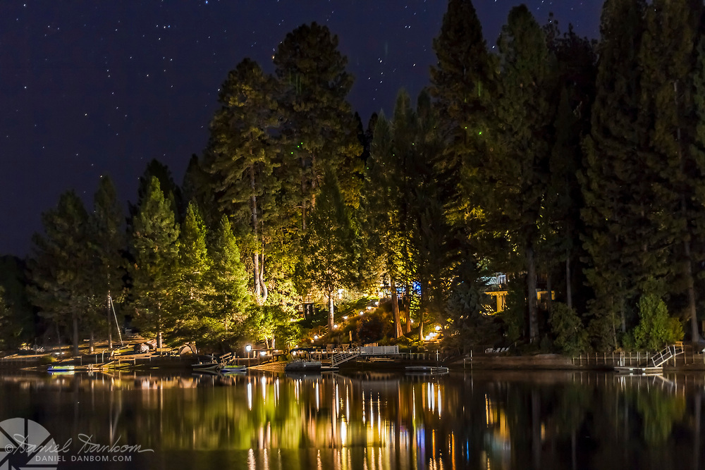 Pine Mountain Lake, near Groveland, California on Highway 120, night view of shore and reflections, with a starry night sky.