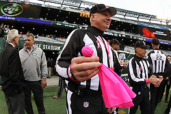Oct 28, 2012; East Rutherford, NJ, USA; Umpire Butch Hannah (40) shows the pink flag presented to him by 11 year old Dante Cano before the game between the New York Jets and the Miami Dolphins at MetLIfe Stadium.