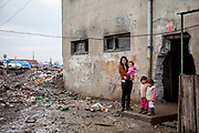 Portrait of a young mother with her child in front of a decrepit building at the Roma settlement in Moldava nad Bodvou. From about 800 inhabitants of the segregated settlement 'Budulovska Street' are roughly 392 children up to the age of 16 years (2014) .