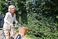 Active senior woman riding bicycle in backyard
