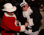 Santa Brian Young (left) takes on Bah Humbug Chris Renne of Seattle, Washington at the Dublin Pub during the Santa Claus Pub Crawl through the Oregon District in downtown Dayton, Saturday, December 11, 2010.