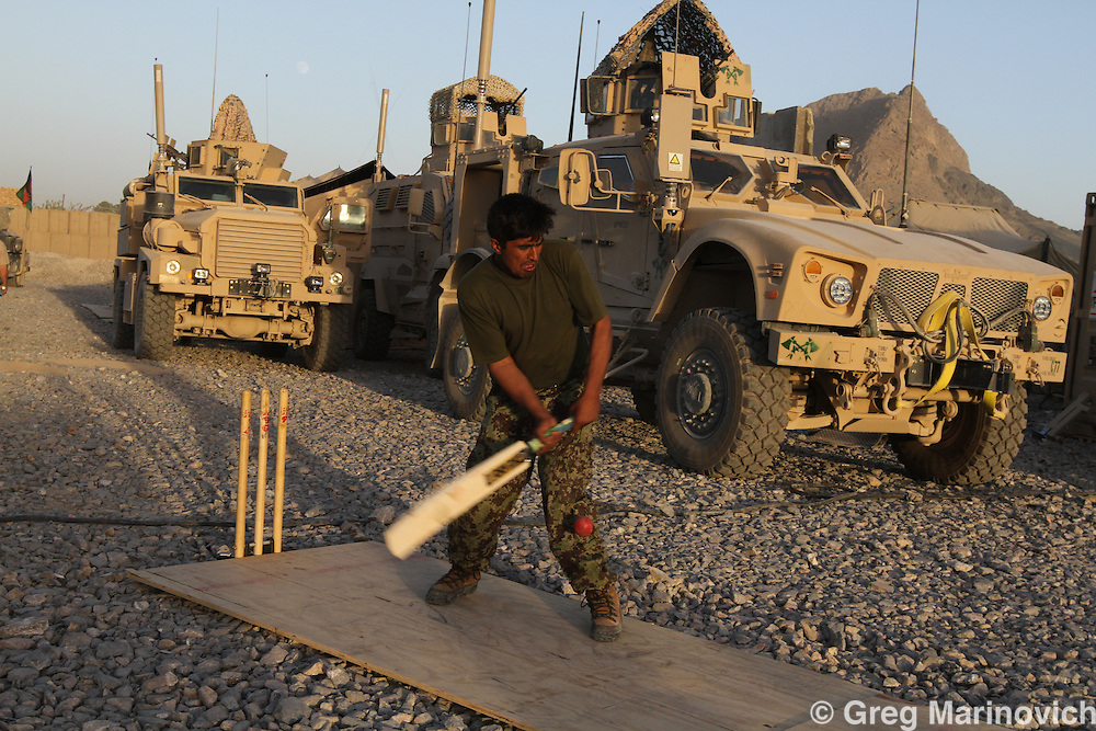 Afghanistan, Kandahar province, Arghandab district, Combat Outpost Caron, 21st Oct 2010. Afghan National Army soldiers play cricket at COP Caron. They are based with Taskforce 1-66 (66th Armoured Regiment), 4th Infantry Div. Charlie company.  Photo Joao Silva.