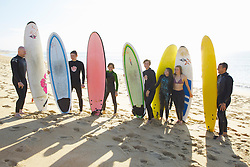 Group of Surfers Standing on Beach Holding Surfboards