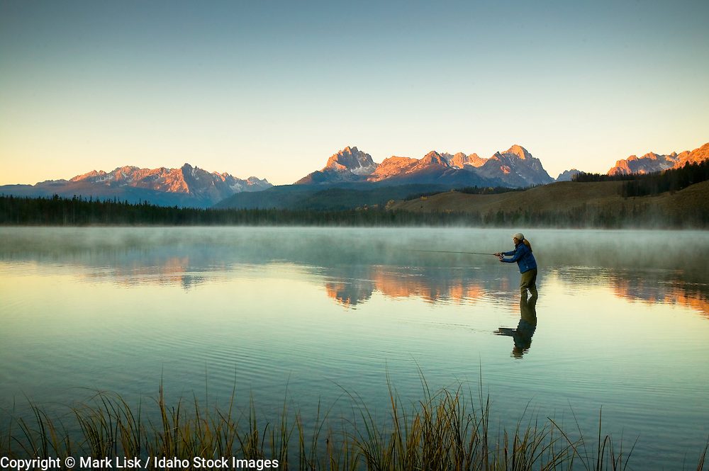 (MR) The fog rising from,  Little Redfish Lake in central Idaho, invites a woman fly fisherman to brave the cool temperatures of a beautiful fall morning.