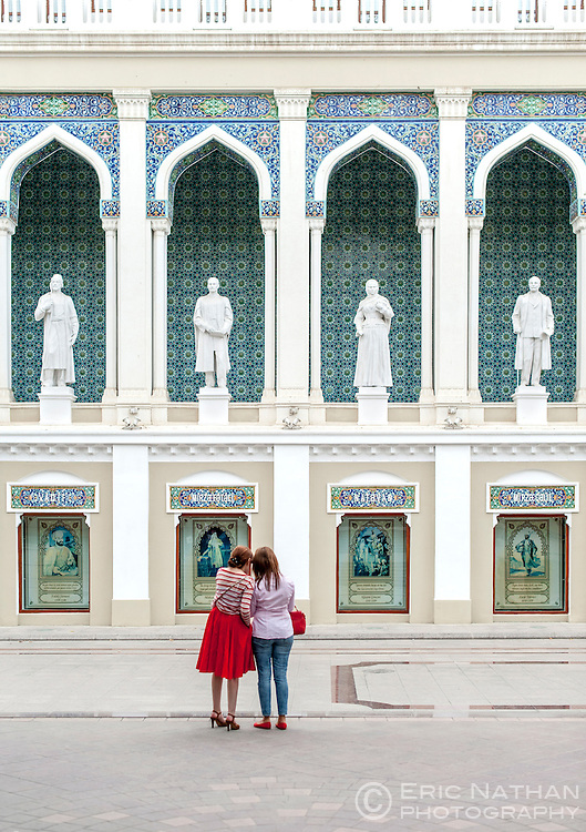 Two women standing in front of the Nizami Museum of Azerbaijan Literature in Baku.